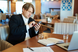 Portrait of confident middle-aged white collar worker dialing number of his business partner while working in cyber cafe