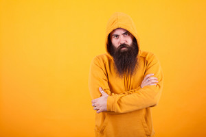 Portrait of dangerous man with long beard wearing a hoodie over yellow background. Handsome man. Stylish man.