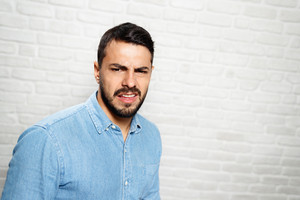 Portrait of disgusted man, hispanic guy showing disgust for bad smell or taste. Copy space