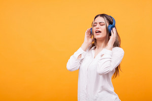 Portrait of excited girl singing and listening music on blue headsphones on yellow background. Having fun
