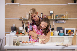 Portrait of excited mom and daughter having fun while cooking. Food pleasure.