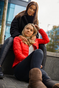Portrait Of Fashionable Friends Sitting Togehter In City