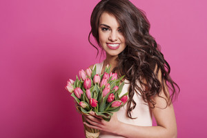 Portrait of gorgeous natural woman with pink tulips
