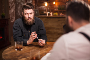 Portrait of handsome bearded man shuffling game cards in a pub. Glass of whiskey, Stylish man. Elegant man.