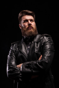 Portrait of Handsome bearded man wearing a leather jacket with serious expresion over black background. Attractive man. Stylish beard.