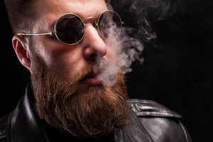 Portrait of handsome bearded man with stylish hair over black background. Serious man. Electronic cigarette.