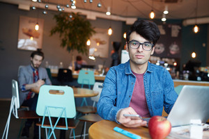 Portrait of handsome young man wearing glasses and jeans jacket looking at camera while working with laptop and smartphone at table in cafe