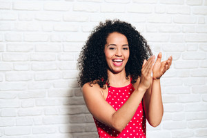 Portrait of happy african american woman clapping hands at show. Black girl having fun, giving applause. Cheerful person smiling for joy and shouting bravo