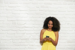 Portrait of happy African American woman smiling against white brick wall and chatting on mobile phone.