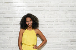 Portrait of happy African American woman smiling against white wall as background, copy space