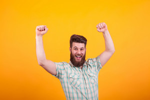 Portrait of happy bearded man with fists up celebratin over yellow background. Hipster young man. Confident man.