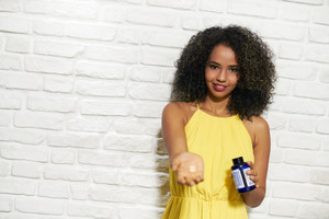 Portrait of happy black woman looking at camera and pouring vitamin pills into hand. Copy space