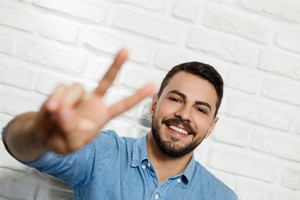 Portrait of happy man smiling. Italian guy winking at camera and doing thumbs up and okay sign with fingers