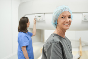 Portrait of happy middle aged patient looking at camera before MRI in hospital lab. Woman smiling in clinic before medical treatment.