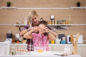 Portrait of happy mother and daughter smiling while cooking. Healthy eating .