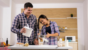 Portrait of happy young couple cooking together in the kitchen at home. Moments together