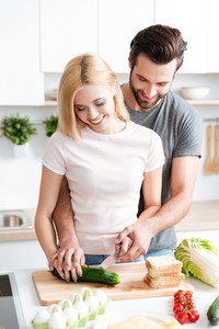 Portrait of happy young couple cooking together in the kitchen at home