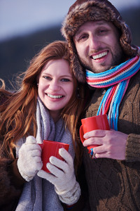 portrait of happy young couple outdoor on winter day drinking warm tea