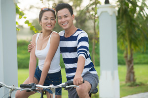 Portrait of happy young couple riding bicycles in the park