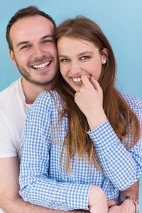 portrait of happy young loving couple looking at camera isolated on blue Background