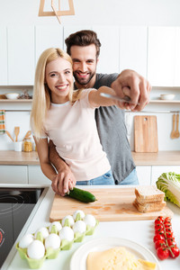 Portrait of happy young smiling couple cooking together in the kitchen at home