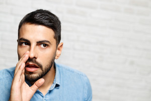 Portrait of Italian man whispering secrets. Guy looking at camera and doing hand gesture for gossip