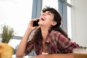 Portrait of laughing woman talking on the phone