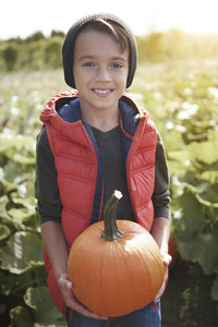 Portrait of little boy with pumpkin