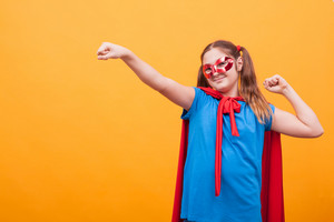 Portrait of little girl in superhero costume over yellow background. Red cape. Red mask. Happy childhood.