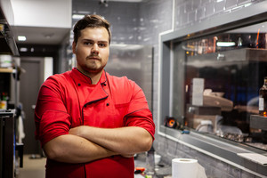 Portrait of male cook chef in kitchen in a restaurant with red clothes