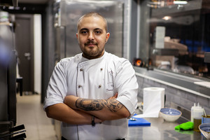 Portrait of male cook chef in kitchen of restaurant