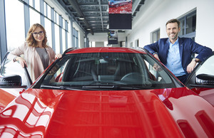 Portrait of mid couple with red car