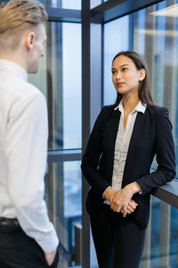 Portrait of mixed race young businesswoman in formalwear standing at panoramic window while having informal meeting with her colleague