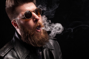 Portrait of nice man playing with cigarette smoke over black background. Handsome rocker.