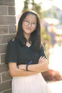 portrait of pretty asian teenager wearing eye glasses looking with eye contact to camera