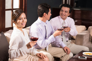 Portrait of pretty businesswoman holding a glass of wine while spending time with her coworkers in the bar