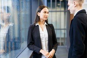 Portrait of pretty young businesswoman chatting with her male colleague while standing at panoramic window of office lobby
