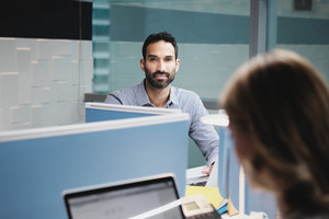Portrait of serious male manager working in modern office with female colleagues. Busy hispanic business man leaning on desk at work in executive coworking space, looking at camera.