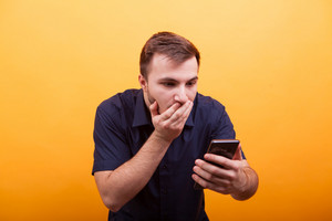 Portrait of shocked young man looking at mobile phone isolated on yellow background. Holding cell phone