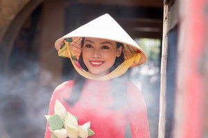 Portrait of smiling beautiful Vietnamese woman wearing conical hat