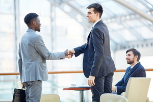 Portrait of smiling successful businessman greeting African-American man in meeting shaking hands at table in office building
