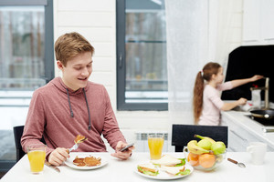 Portrait of smiling teenage boy texting with his friend on smartphone while sitting in kitchen and eating pancakes, his little sister standing at sink and washing dishes