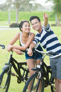 Portrait of sporty Vietnamese couple with bikes where man pointing at something