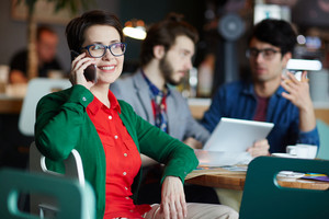 Portrait of three creative people dressed in business casual at table in cafe, focus on young businesswoman wearing glasses and smiling cheerfully while talking by phone