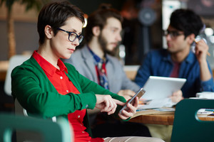 Portrait of three creative people dressed in business casual at table in cafe, focus on young businesswoman wearing glasses using smartphone