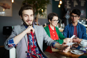 Portrait of three creative people dressed in business casual at table in cafe, focus on young smiling businessman with long hair smiling cheerfully looking at camera