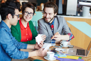 Portrait of three creative people dressed in business casual smiling and discussing project while working at table during meeting
