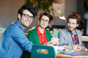 Portrait of three creative people dressed in business casual working at table during meeting, focus on young smiling man wearing glasses