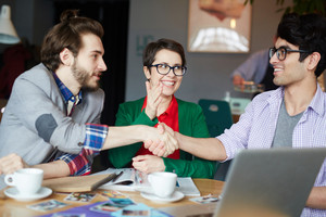 Portrait of three creative people wearing casual clothes during meeting at table, two smiling friends shaking hands making a bet