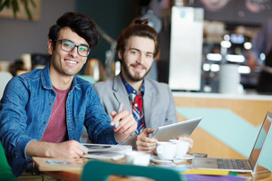 Portrait of two creative young men dressed in business casual smiling looking at camera while working at table during meeting